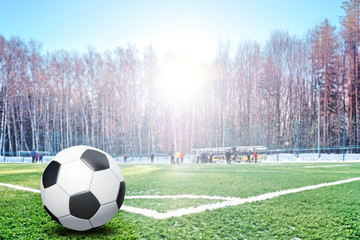 Traditional football ball in corner of soccer pitch field with white snow at winter against...