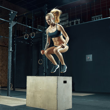 Shot of a young beautiful woman jumping onto a box as part of exercise routine. Fitness woman doing box jump workout at gym. Box jumping workout at modern gym. Powerful attractive muscular woman.