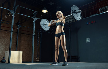 Strong young woman exercising with barbell in a gym Muscular caucasian woman using curved barbell...