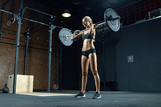 Indoor shot of caucasian female performing deadlift exercise with barbell Confident young blonde woman doing crossfit workout in gym. Female performing deadlift exercise with weight bar Concept photo.