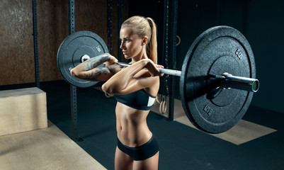 Indoor shot of caucasian female performing deadlift exercise with barbell Confident young blonde woman doing crossfit workout in gym. Female performing deadlift exercise with weight bar Concept photo. Wall mural