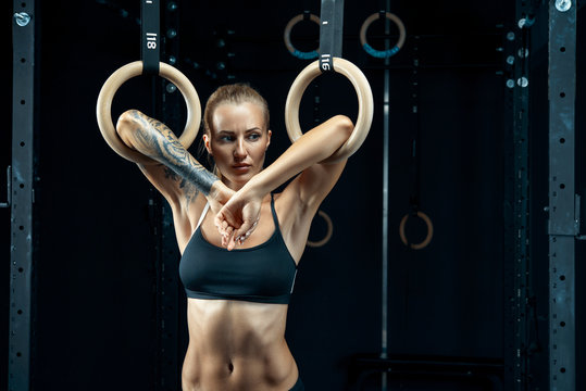 Strong young woman in a black sports top holding gymnast rings at the gym and looking down Young caucasian female prepare to exercise with dip rings. Concept: power, strength, healthy lifestyle, sport