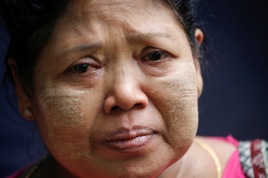 A family of one of the members of Peacock Generation, a satirical poetry troupe, cries while talking to media from a court room in Botataung court in Yangon