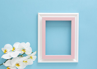 Empty frame and flowers orchid flat lay on blue pastel background with copy space. Minimal concept.