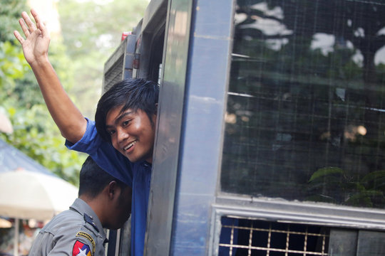 Zayar Lwin, a member of the Peacock Generation, a satirical poetry troupe, waves to the media and crowd, in a police van outside of Botataung court in Yangon