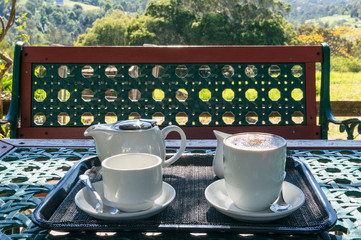 Two white cups and tea pot on a table outside. Coffee break nature background