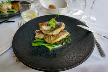 Dark plate with grilled fish fillets and green vegetables