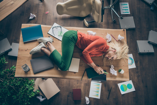 High angle above view photo of corporate messy atmosphere unorganized blond business lady lying table don't mind cluttered office texting telephone wear casual outfit indoors