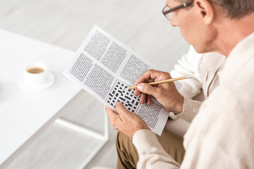selective focus of senior man with dyslexia holding pencil and crossword
