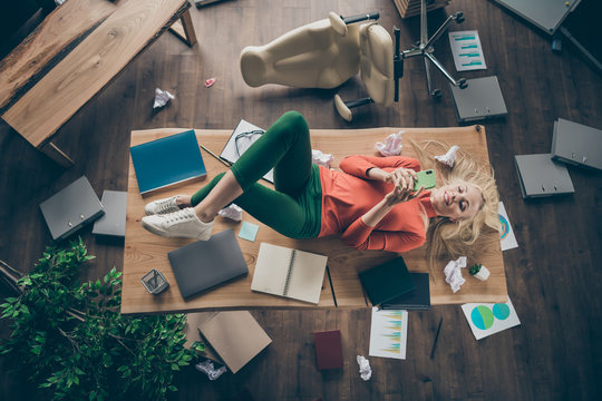 High angle view photo of corporate messy atmosphere careless blond business lady lying table don't mind cluttered office disorder texting telephone wear casual outfit indoors