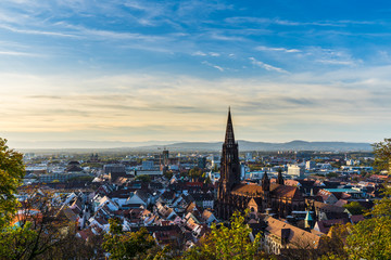 Germany, Freiburg im breisgau skyline with famous cathedral muenster in old town in warm sunset sun light in autumn season, aerial view above cityscape