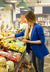 Woman choosing a dairy products at supermarket. Reading product information.  Concept of information of eating products, organic fruit and vegetables