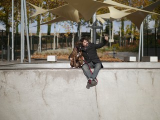 man with black coat and beard makes a picture of boxer dog in a skate park in a park on a cloudy autumn day