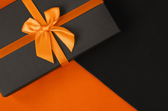 A stylish gift box on duotone orange and black background with copy space