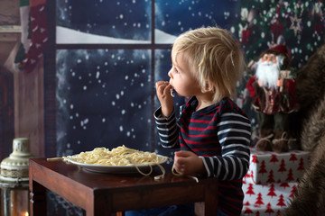 Sweet toddler child, boy, eating spaghetti at home