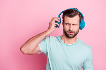 What is it. Frustarted music lover man disdlike his playlist song he listen from blue modern headset feel confused expression wear casual style clothes isolated over pink color background
