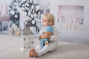 Beautiful blonde toddler boy, dressed in white in decorated white room for Christmas