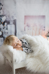 Beautiful toddler child, baby boy, sleeping on Christmas eve at home