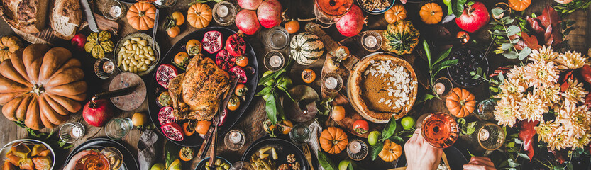 Poster de jardin Nourriture Family celebrating Thanksgiving day. Flat-lay of peoples hands with glasses of rose wine over Friendsgiving table with Autumn food, roasted turkey and pumpkin pie over wooden table, wide composition
