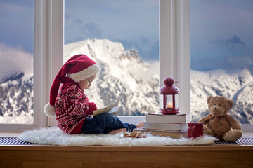 Sweet blonde child, boy, sitting on window shield with teddy bear friend toy, reading book and...