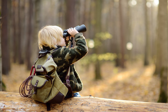Little boy scout with binoculars during hiking in autumn forest. Child is sitting on large fallen tree and looking through a binoculars.