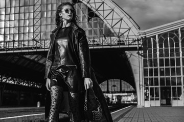 Outdoor monochrome, black and white  fashion portrait of young confident model, woman wearing trendy leather trench coat, dress, glasses, with small  bag, walking in street of city. Copy, empty space Wall mural