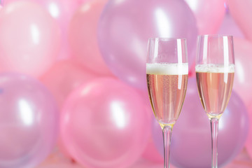 Champagne glasses on pink bubbles background. Christmas and New Year holidays background.