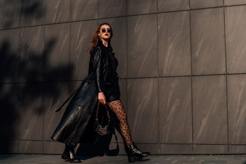 Outdoor full-length fashion portrait of young confident woman wearing total black leather outfit, leopard print tights, holding small bag, walking  in city street, grey urban background. Copy space Papier Peint