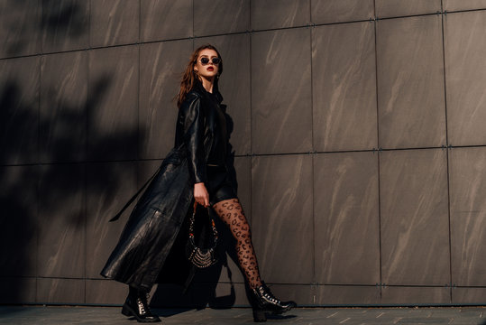 Outdoor full-length fashion portrait of young confident woman wearing total black leather outfit, leopard print tights, holding small bag, walking  in city street, grey urban background. Copy space