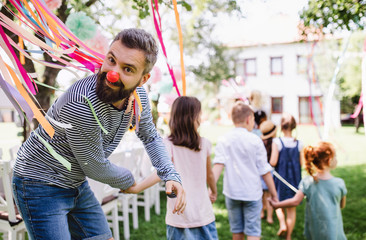 Man with kids on birthday party playing outdoors in garden in summer.