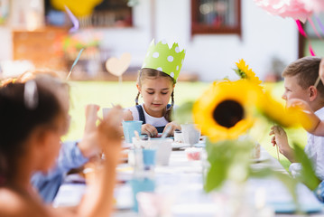 Small children sitting at the table outdoors on garden party in summer, eating.