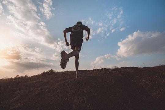 Runners running fitness in woods.athlete running on trail stones.