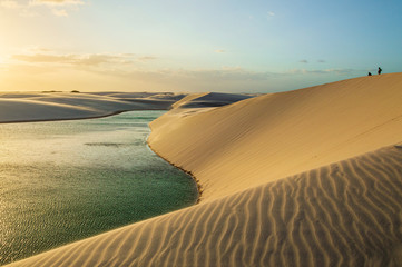Sunset upon river crossing white dunes in Brazil