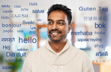 communication, translation and international concept - smiling indian man in knitted woolen sweater...