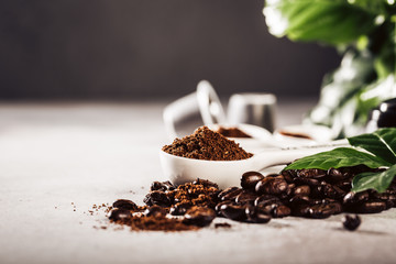 Background with measuring spoon with coffee, beans and leafs. Beverage cafe shop concept with copy space. Toned photo