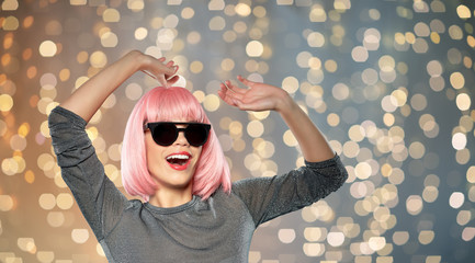 style, fashion and people concept - happy laughing young woman in pink wig and black sunglasses...