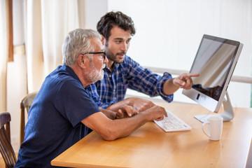 man teaching elderly man to using computer    - fototapety na wymiar