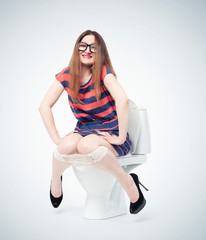 Happy young girl in glasses sits on the toilet. Situation concept.