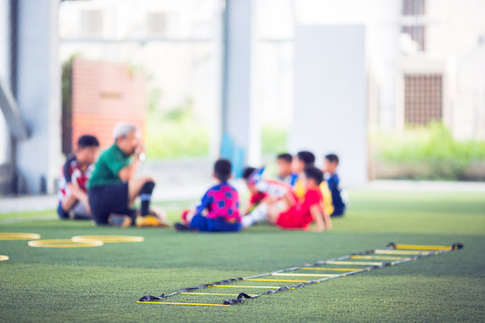 Selective focus to ladder drills on green artificial turf with blurry coach and kid soccer are training, blurry kid soccer jogging between marker cones and control ball.