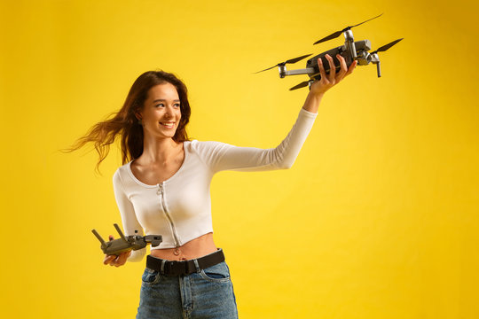 Teen girl launches aerial drone quadcopter. Isolated on a yellow background. Aerial photography.