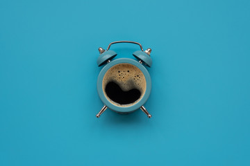Alarm clock as coffee cup on blue background. Top view. Flat lay. Good morning concept Fotomurales