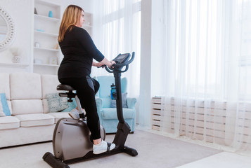 Model - a fat woman, at home engaged in a stationary bike. Fototapete