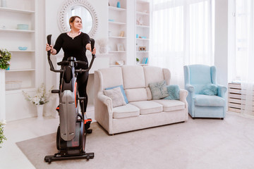 Model - a fat woman, trying to lose weight and at home is engaged in an elliptical trainer