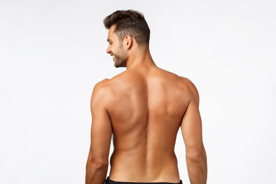 Health, bodybuilding and fitness concept. Rear view, handsome confident young caucasian guy, muscular athlete from behind, showing back muscles, turn face left and smiling, white background