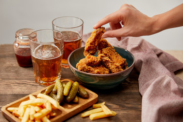 cropped view of woman eating delicious chicken nuggets, french fries and gherkins near glasses of beer on wooden table isolated on grey