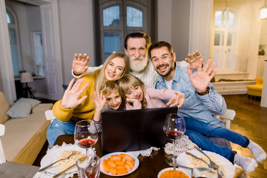 Happy milti generation family watching photos or movie on a laptop while sitting at the festive table with dinner meal. Holidays, healthy food and positive emotion, family concept.