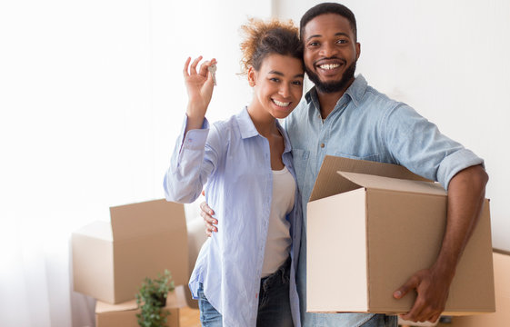 Couple Showing Key Holding Moving Box Standing In New Home