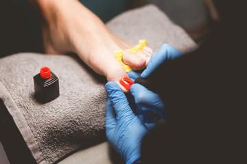 Master does pedicure for client. Pedicure process. Girl draws toenails