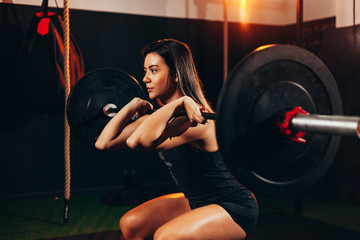 Muscular woman in gym doing heavy weight exercises. Young woman doing weight lifting at health club