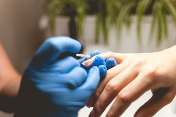 Manicurist varnishes the client's nails, making french style. Manicure process close up